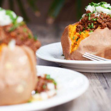 enchilada stuffed sweet potatoes served on white plates