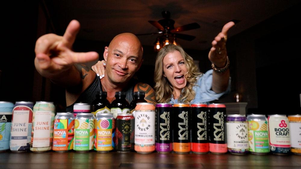 woman and man behind cans of hard kombucha on a bar